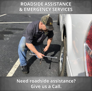 tow trucker driver changing a tire and offering emergency roadside assistance
