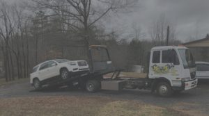 white SUV being loaded onto flatbed tow truck